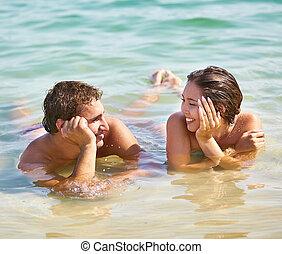 Resort romance - Tanned guy and girl flirting enjoying their...