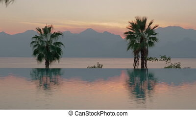 Resort scene at sunset. Swimming pool with palms, sea and...