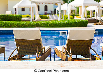 Resort swimming pool with deck chairs