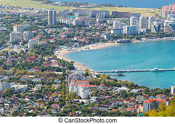Resort town. Bird's-eye view. Sunny day in Gelendzhik. Turquoise water of the sea bay and sand beach with many people in frame. Velvet season.