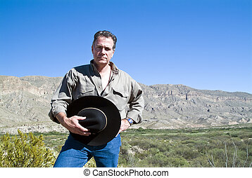 A man standing with his hat in his hand in a gesture of respect for the rugged beauty surrounding him.
