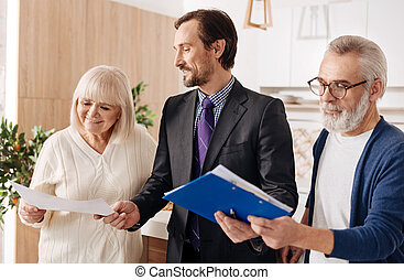 Respectable lawyer demonstrating contract for aged couple of clients