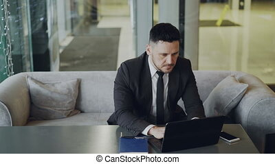 Respected Caucasian businessman in black business suit sitting and working concentrated on his laptop computer in modern cafe