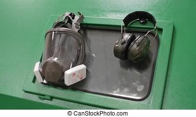 Respirator hanging on metal box. Respirator and headphones...