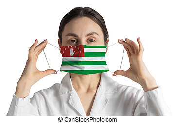 Respirator with flag of Abkhazia Doctor puts on medical face mask isolated on white background