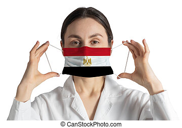 Respirator with flag of Egypt Doctor puts on medical face mask isolated on white background