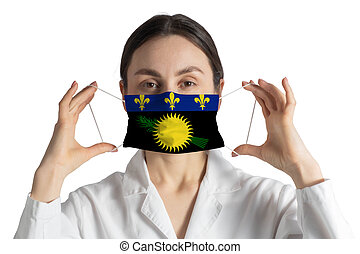 Respirator with flag of Guadeloupe Doctor puts on medical face mask isolated on white background