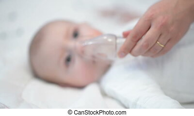 Respiratory Therapy - Baby taking respiratory therapy. Hand...
