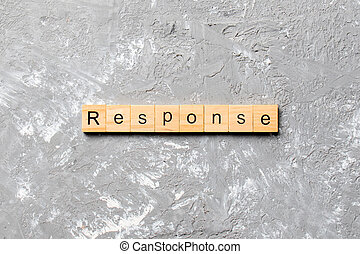 RESPONSE word written on wood block. RESPONSE text on cement table for your desing, concept