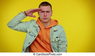 Yes sir. Subordinate responsible serious stylish boy giving salute listening to order as if soldier, following discipline, obeying, expressing confidence. Young man on yellow studio wall background