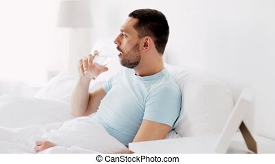 man drinking water in bed at home - rest and people concept...
