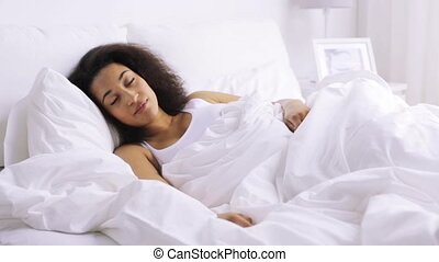 african woman sleeping in bed at home bedroom