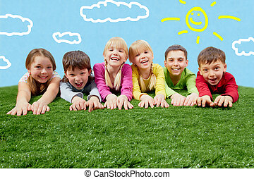 Rest - Group of happy children lying on a grass and ...