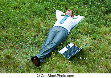 Image of businessman relaxing on the grass with laptop near by