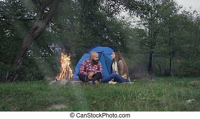 Rest on camping - A man who has a beard and woman with long hair is sitting at the burning fire in a tent town