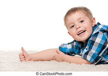 Rest on the white carpet - A smiling little boy is lying on ...