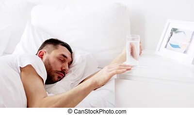 man waking up and drinking water in bed at home - rest,...