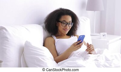 african woman calling on smartphone in bed at home - rest,...