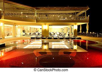 Restaurant and swimming pool in night illumination,...