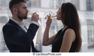 restaurant, couple and holiday concept - smiling couple with glass of champagne looking at each other at restaurant
