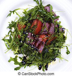Salad with pieces of marbled beef and arugula on a white plate