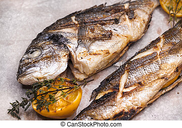 Restaurant dish two grilled fish Dorado and Seabass -...