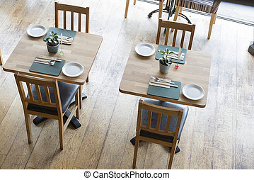 Restaurant furnishings and tableware in a brightly lit dining area