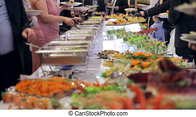 Restaurant guests select food from a buffet