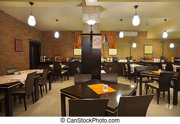 Tables, chairs and brick wall, interior of a restaurant.