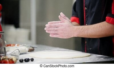 Restaurant kitchen. A chef clapping his hands with flour on...