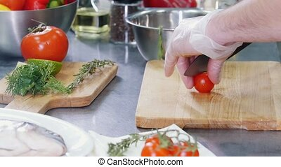 Restaurant kitchen. A chef cutting a cherry tomato in half....