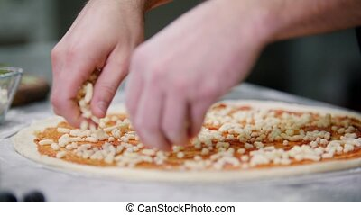 Restaurant kitchen. A chef putting cheese on the pizza. Mid...