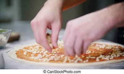Restaurant kitchen. A chef putting cheese pieces on the...