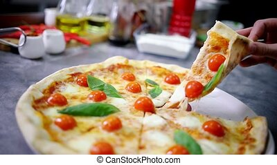 Restaurant kitchen. A person takes a piece of Caesar pizza....