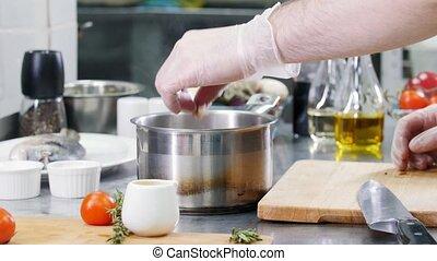 Restaurant kitchen. Adding seafood ingredients in the...