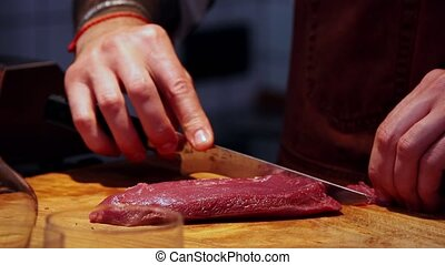 Restaurant kitchen - chef cutting meat in small slices with sharpened knife on the desk