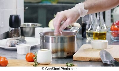 Restaurant kitchen. Chef mixing ingredients in the soup with a spoon