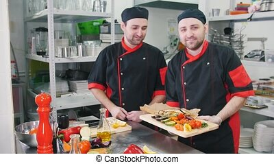 Restaurant kitchen. Two men chefs finished serving the dish,...