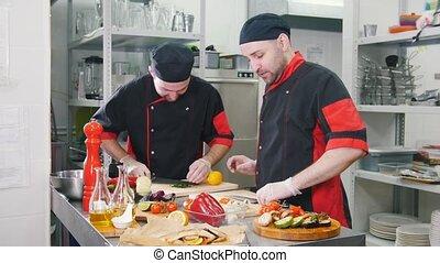 Restaurant kitchen. Two men working on serving dishes...