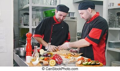 Restaurant kitchen. Two men working on serving fish dish on...