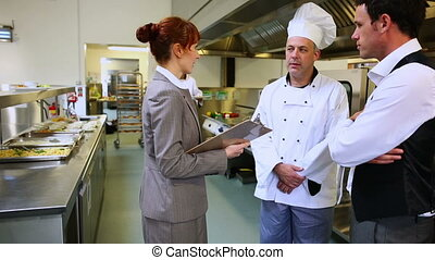 Restaurant manager chatting with waiter and head chef in a commercial kitchen