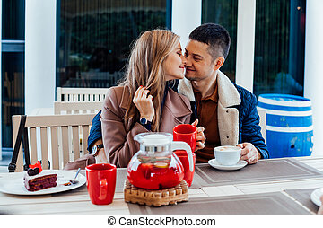 restaurant on the street. a guy with a girl drink hot coffee and tea