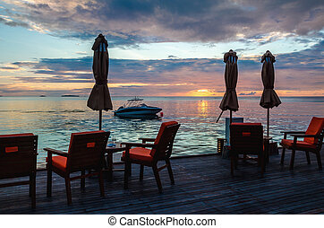 Restaurant on the water on the background of beautiful colorful sunset over the ocean