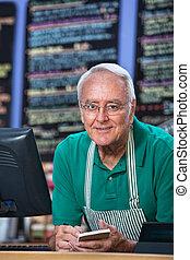 Restaurant Owner Taking Orders - Senior man with apron...