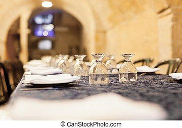 Restaurant Placesetting - Long restaurant table with dishes,...