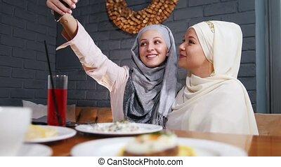 restaurant, prendre, musulman, deux, téléphone, séance, selfie, femmes