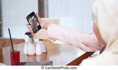 restaurant, prendre, musulman, deux, téléphone, table, séance, selfie, femmes