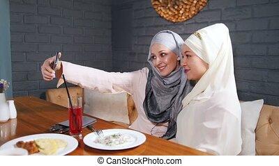 restaurant, prendre, musulman, deux, table, séance, selfie, femmes