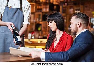Restaurant service. young couple and waiter offerring bottle of a wine