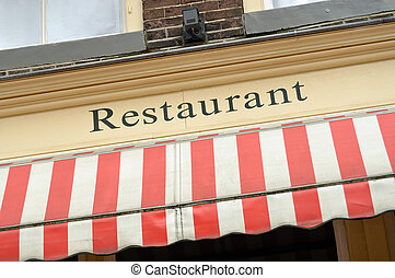 Restaurant sign and red white sunscreen on the facade of a...